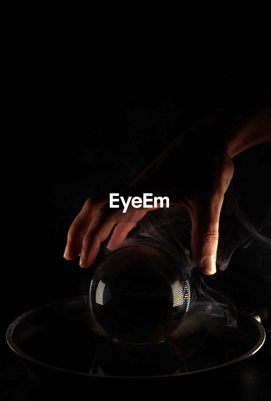 Close-up of hand by crystal ball on table against black background