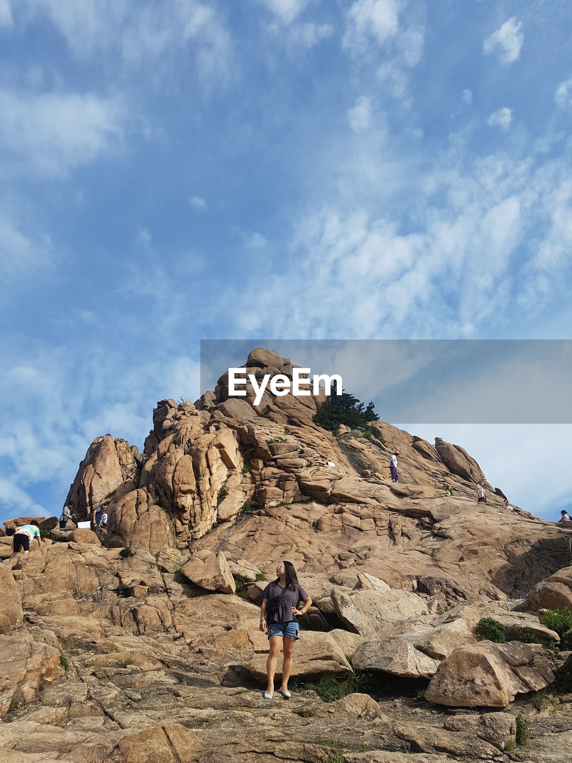 Woman standing on rock formation against cloudy sky