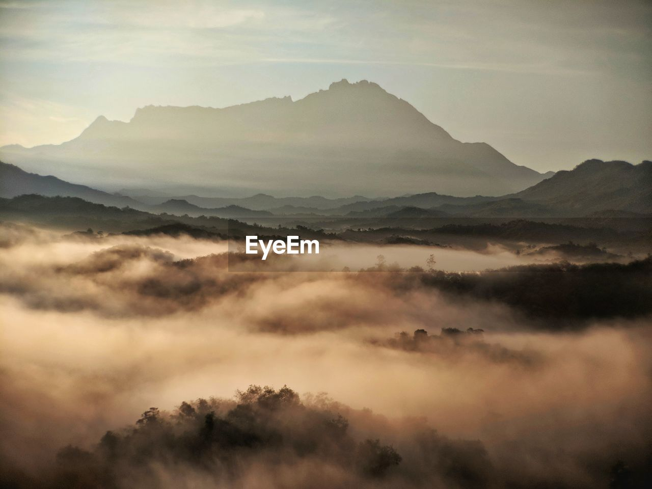 Scenic View Of Mountains In Foggy Weather During Sunset