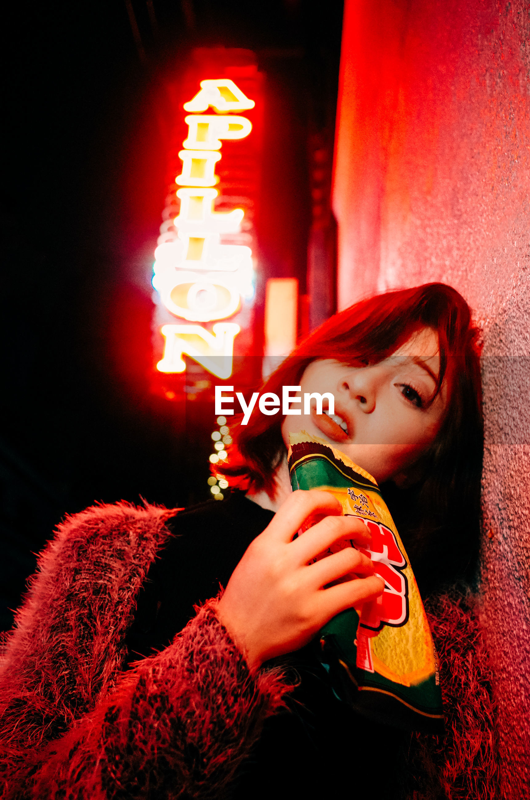 YOUNG WOMAN LOOKING AWAY AT ILLUMINATED RED NIGHT