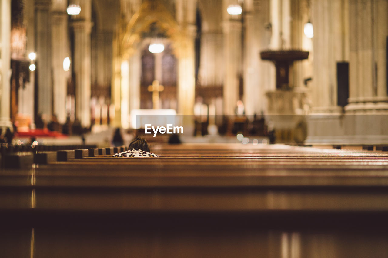 Rear View Of Woman Sitting On Pew In Illuminated Church