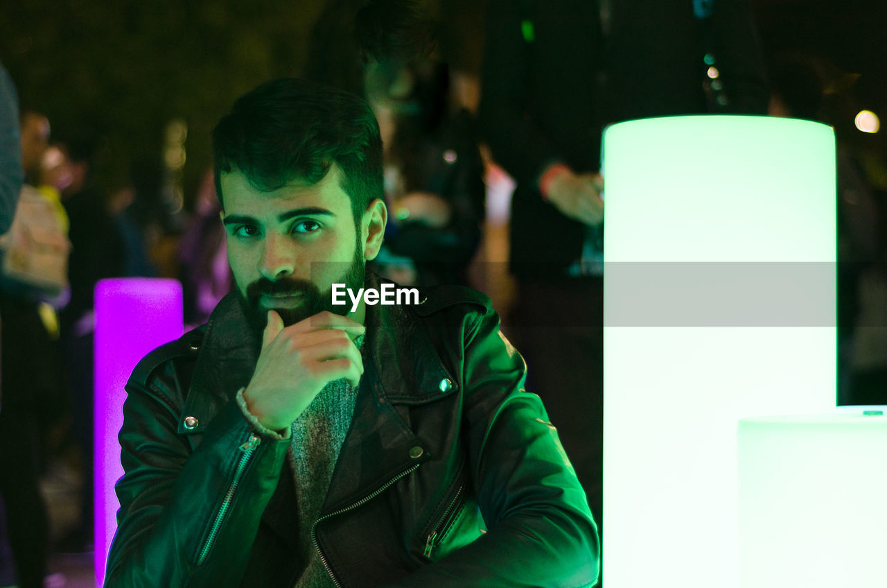 Portrait Of Bearded Young Man Wearing Leather Jacket In Nightclub