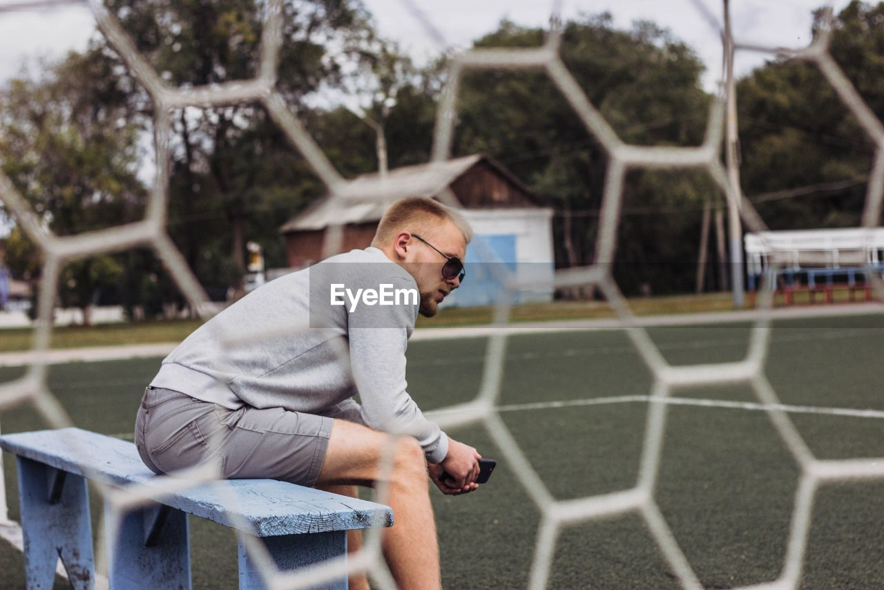 Side view of man sitting on bench seen through net