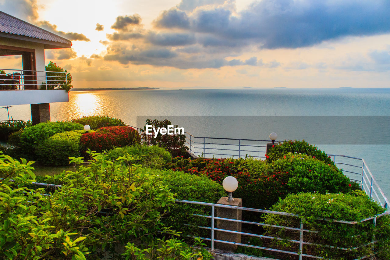 sea, sky, built structure, railing, water, horizon over water, architecture, tranquility, cloud - sky, no people, sunset, building exterior, scenics, tranquil scene, nature, beauty in nature, outdoors, tree, day