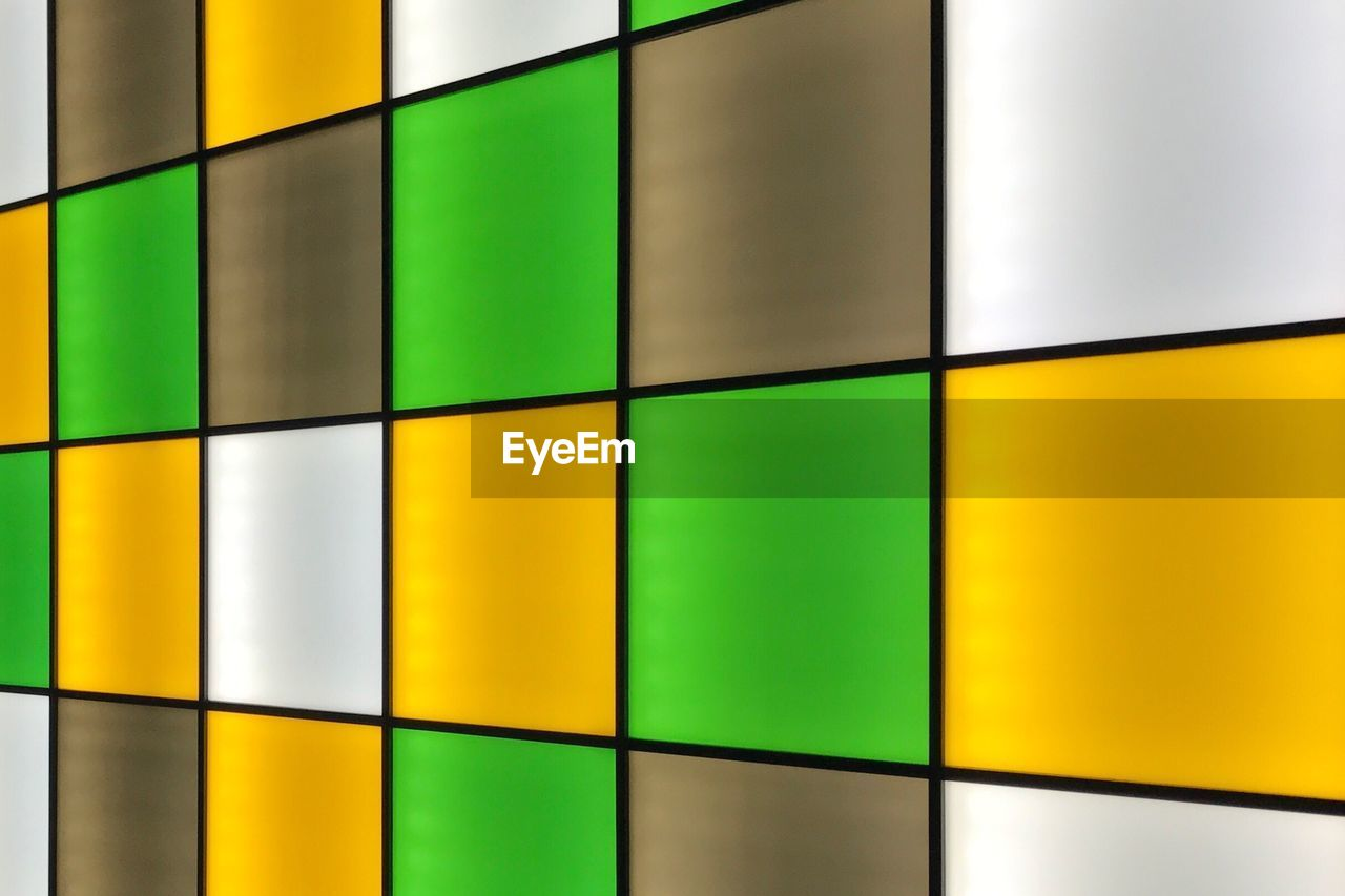 pattern, multi colored, full frame, wall - building feature, backgrounds, shape, design, indoors, no people, yellow, geometric shape, close-up, green color, tile, architecture, flooring, built structure, abstract, focus on foreground, square shape, tiled floor