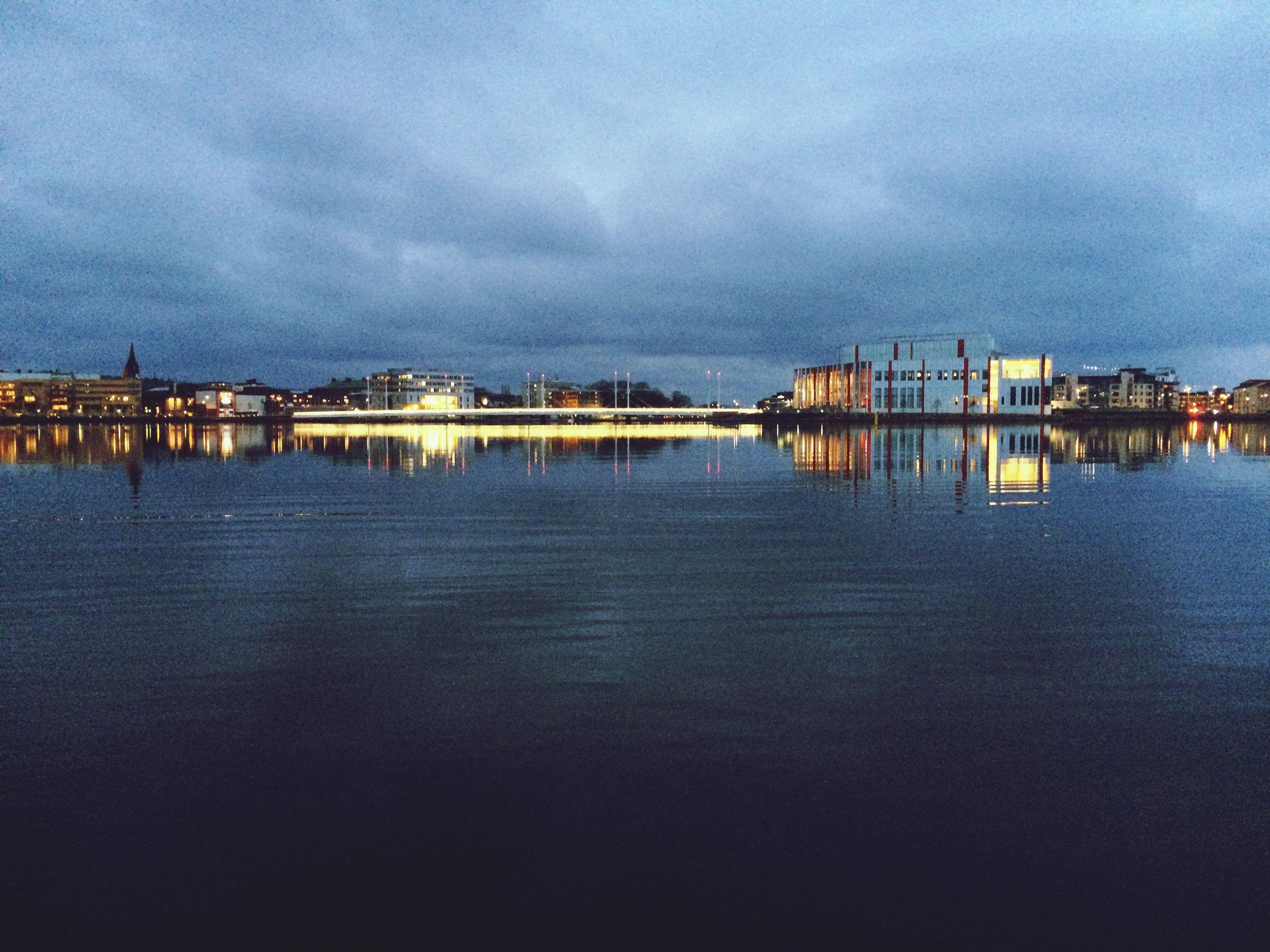 Illuminated city by sea against cloudy sky