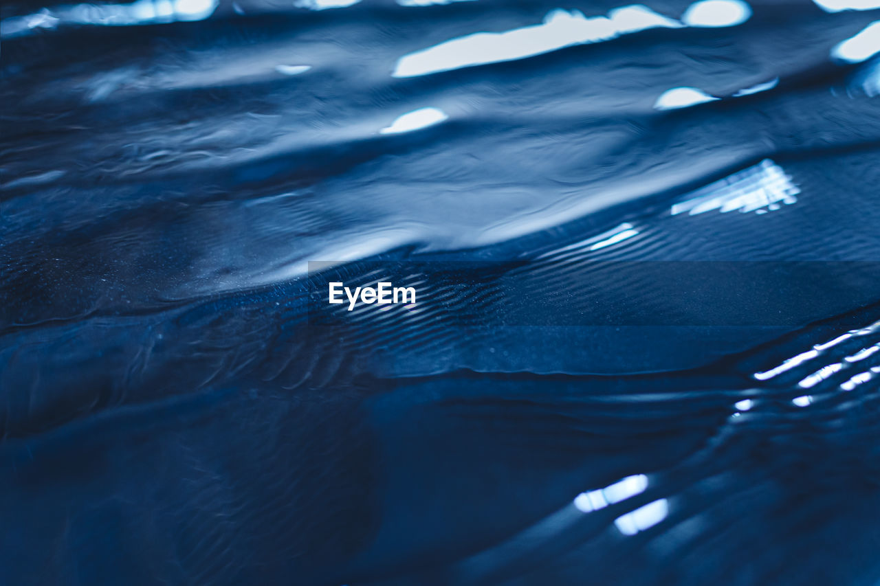 Calm water surface texture with waves in dark blue color. trendy fresh abstract nature background