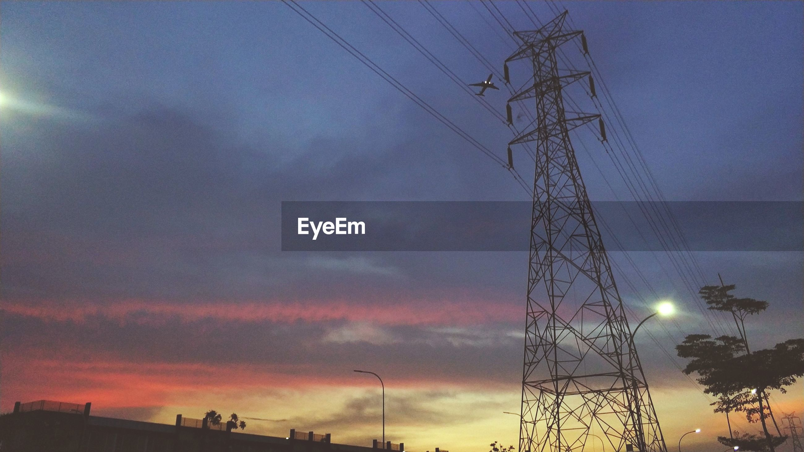 Low angle view of electricity pylon against cloudy sky during sunset