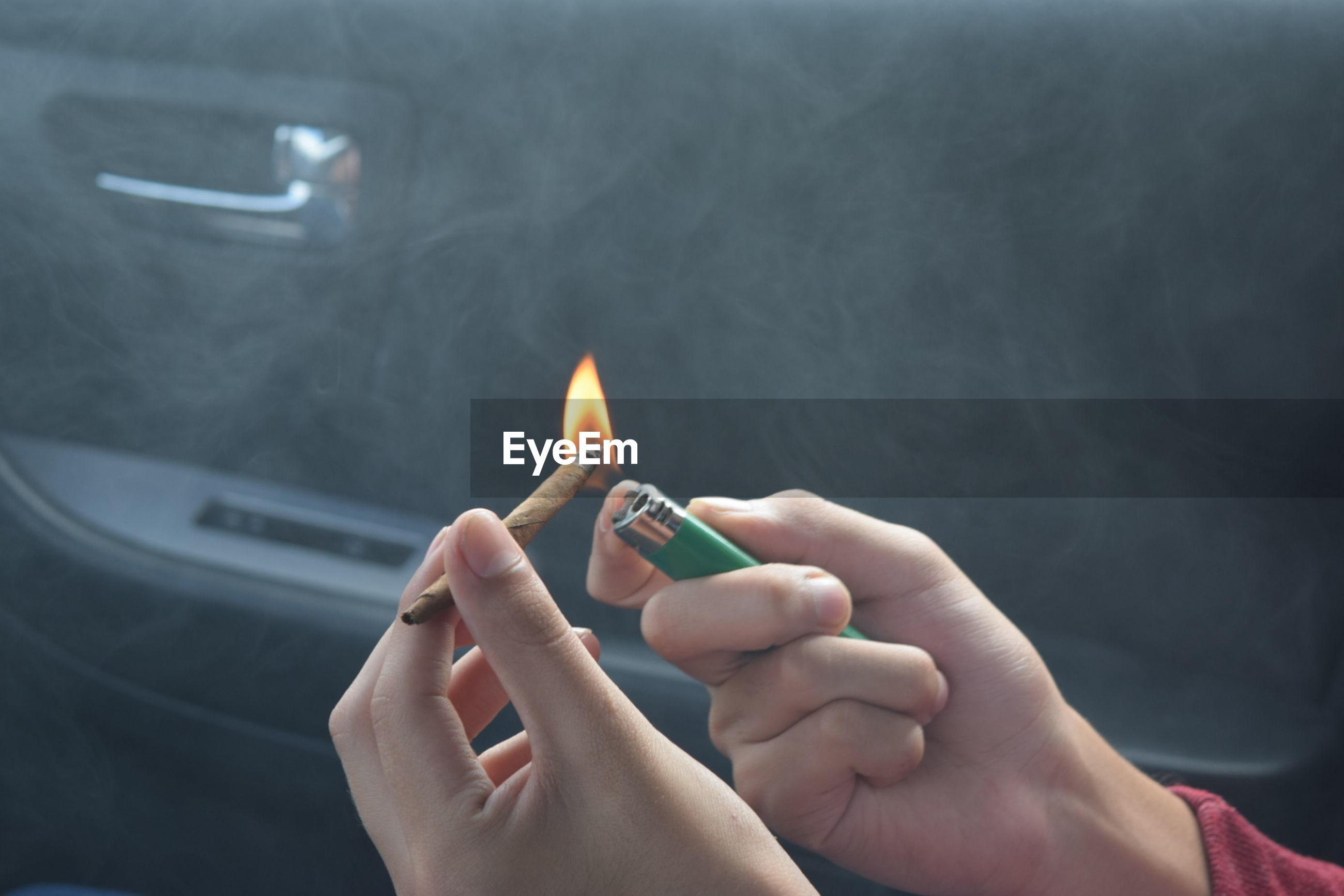 Cropped hands burning marijuana joint in car