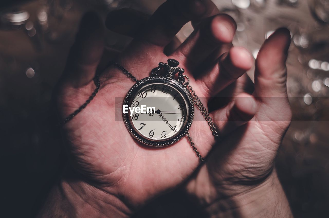 Cropped image of hand holding pocket watch
