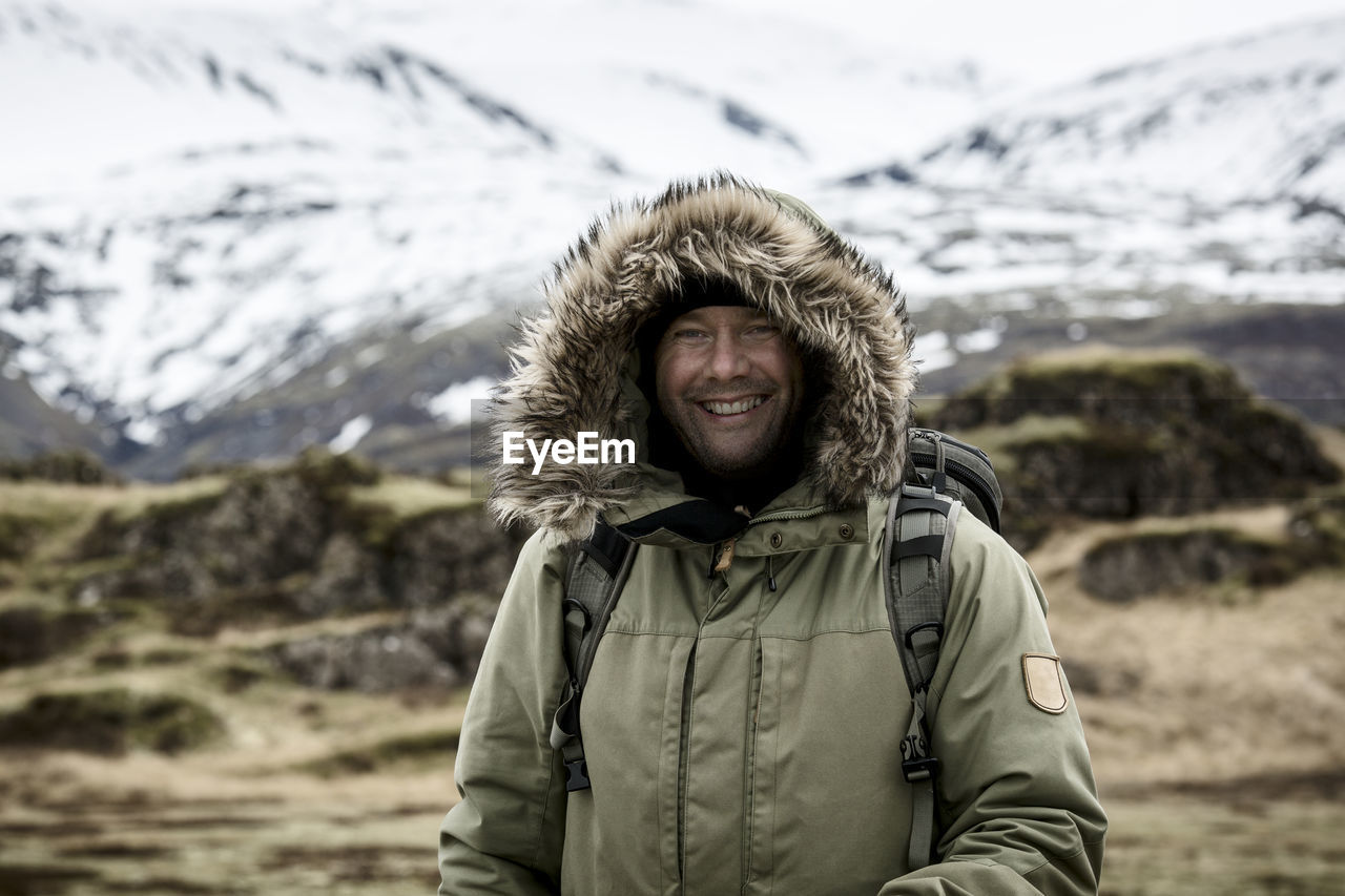 PORTRAIT OF SMILING MAN STANDING ON SNOW