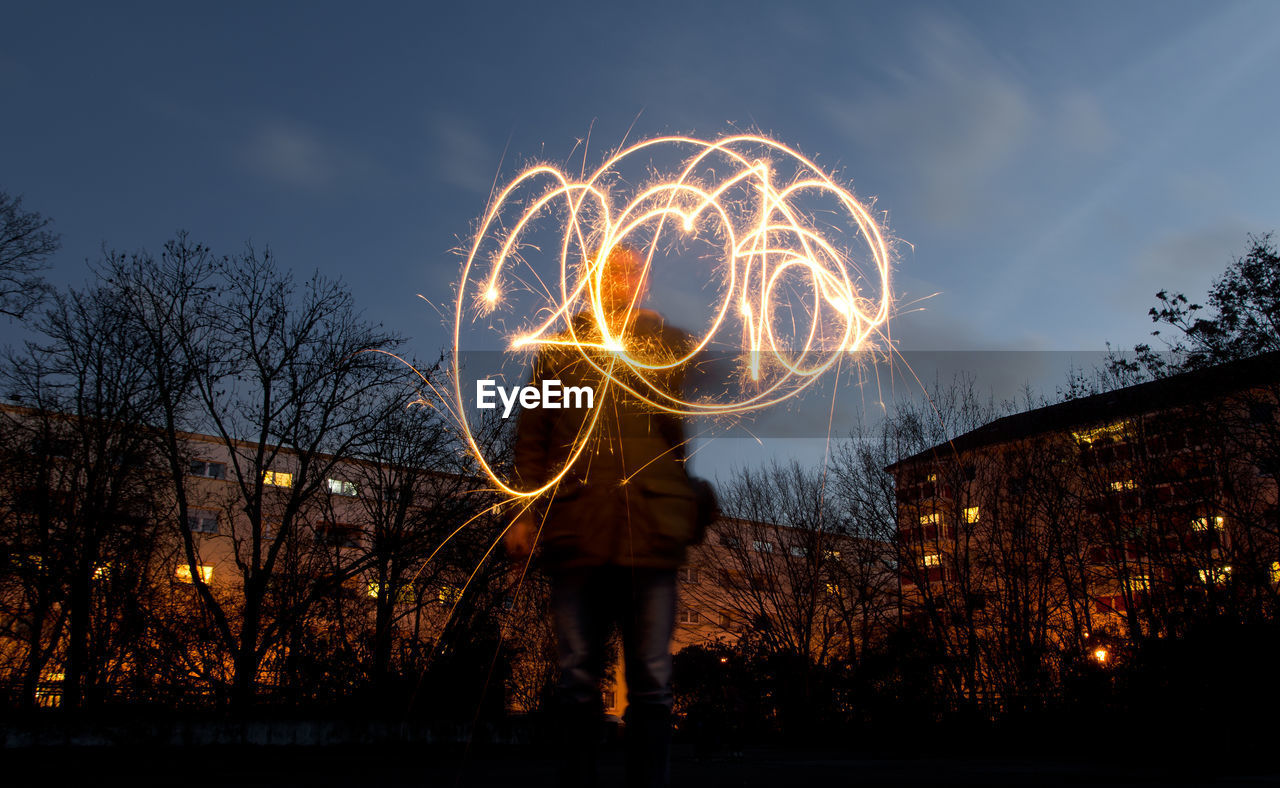 Low angle view of person doing light painting at night