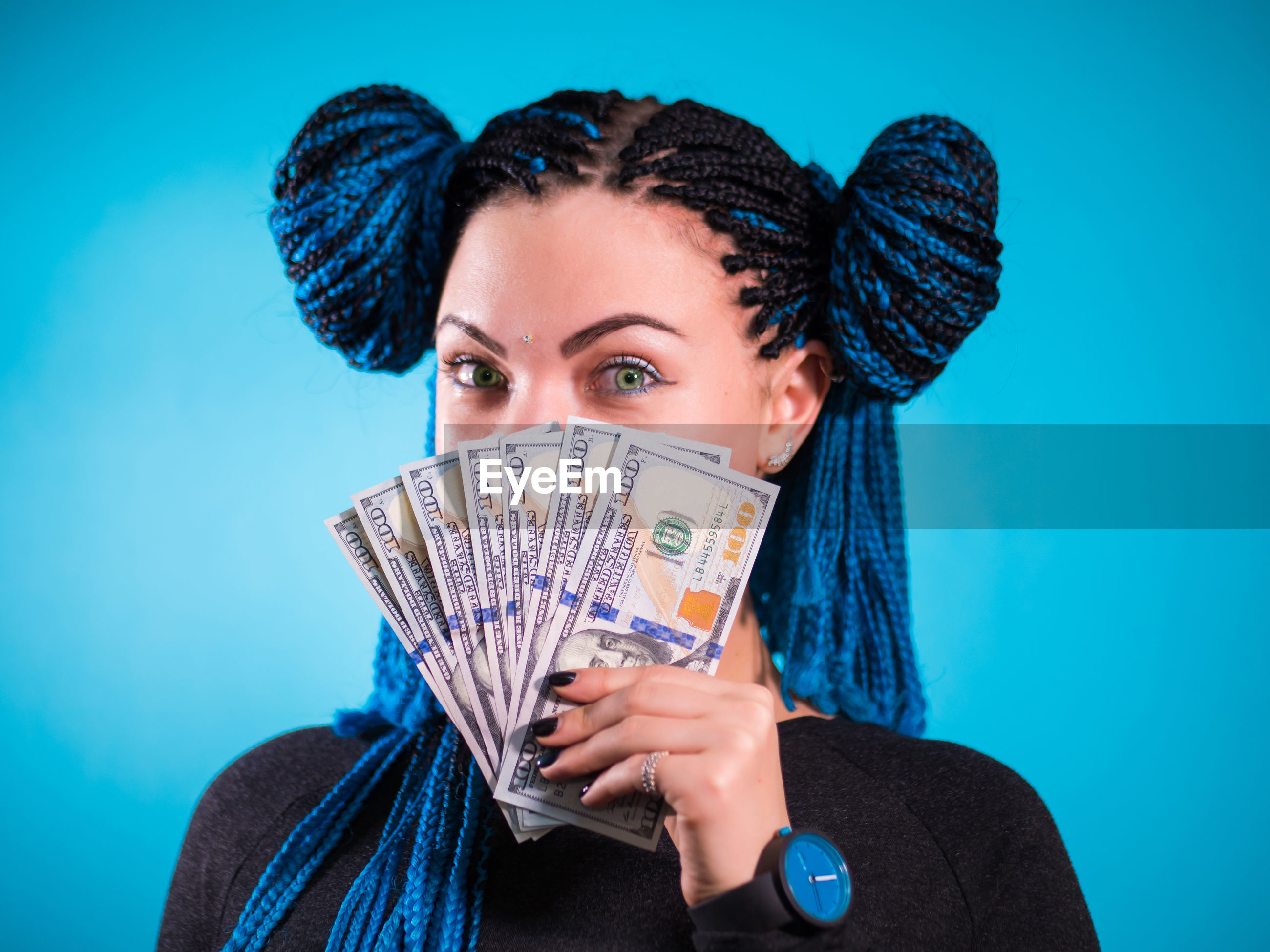 Close-up of young woman holding currency against colored background