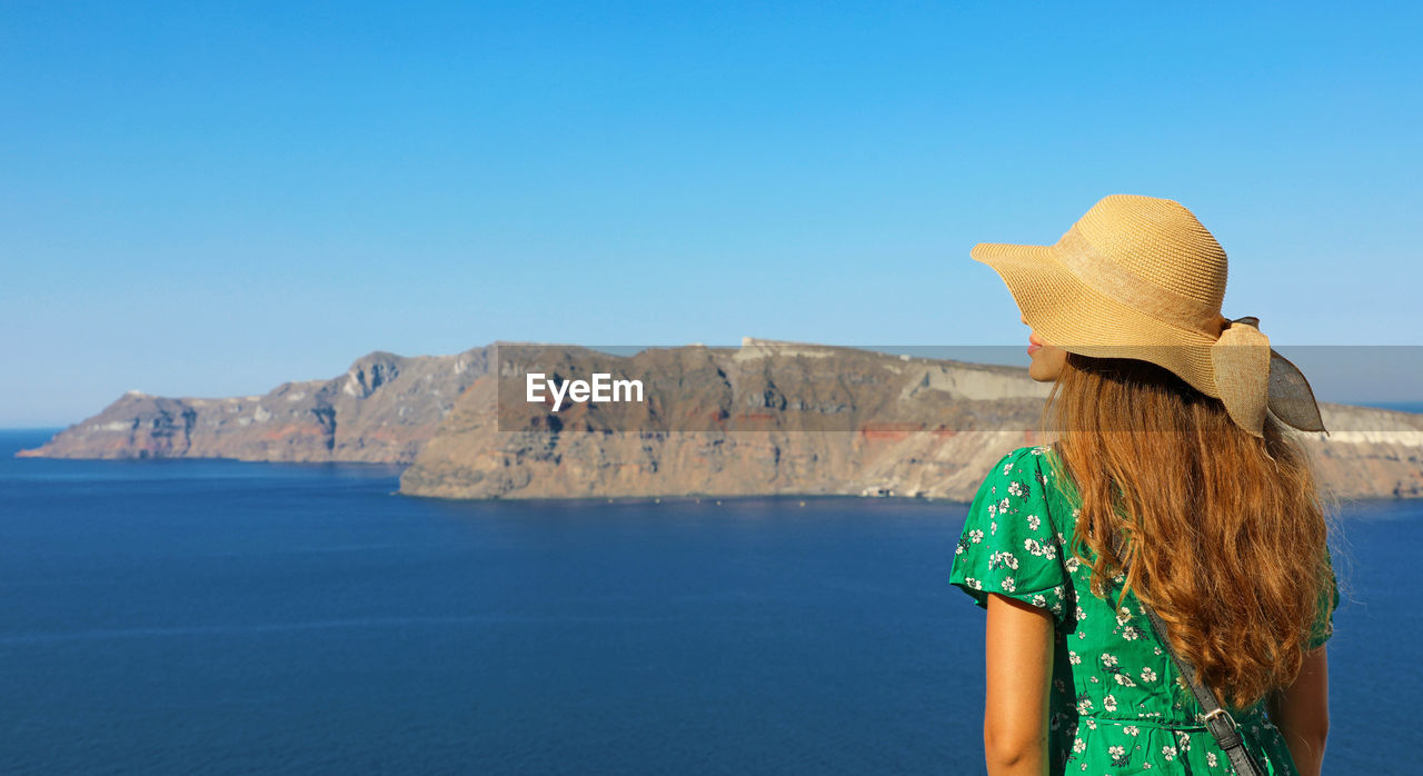 sky, rear view, sea, clothing, hat, water, clear sky, scenics - nature, hair, hairstyle, beauty in nature, nature, one person, blue, day, copy space, lifestyles, leisure activity, tranquil scene, outdoors, looking at view, sun hat