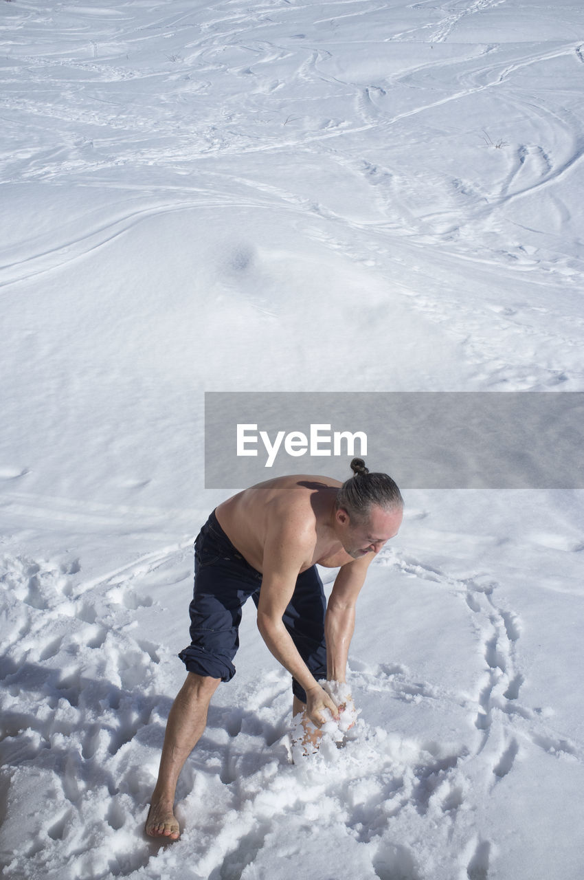 Adult man practicing cryotherapy, in the snow. cryotherapy is a pain treatment that uses a method