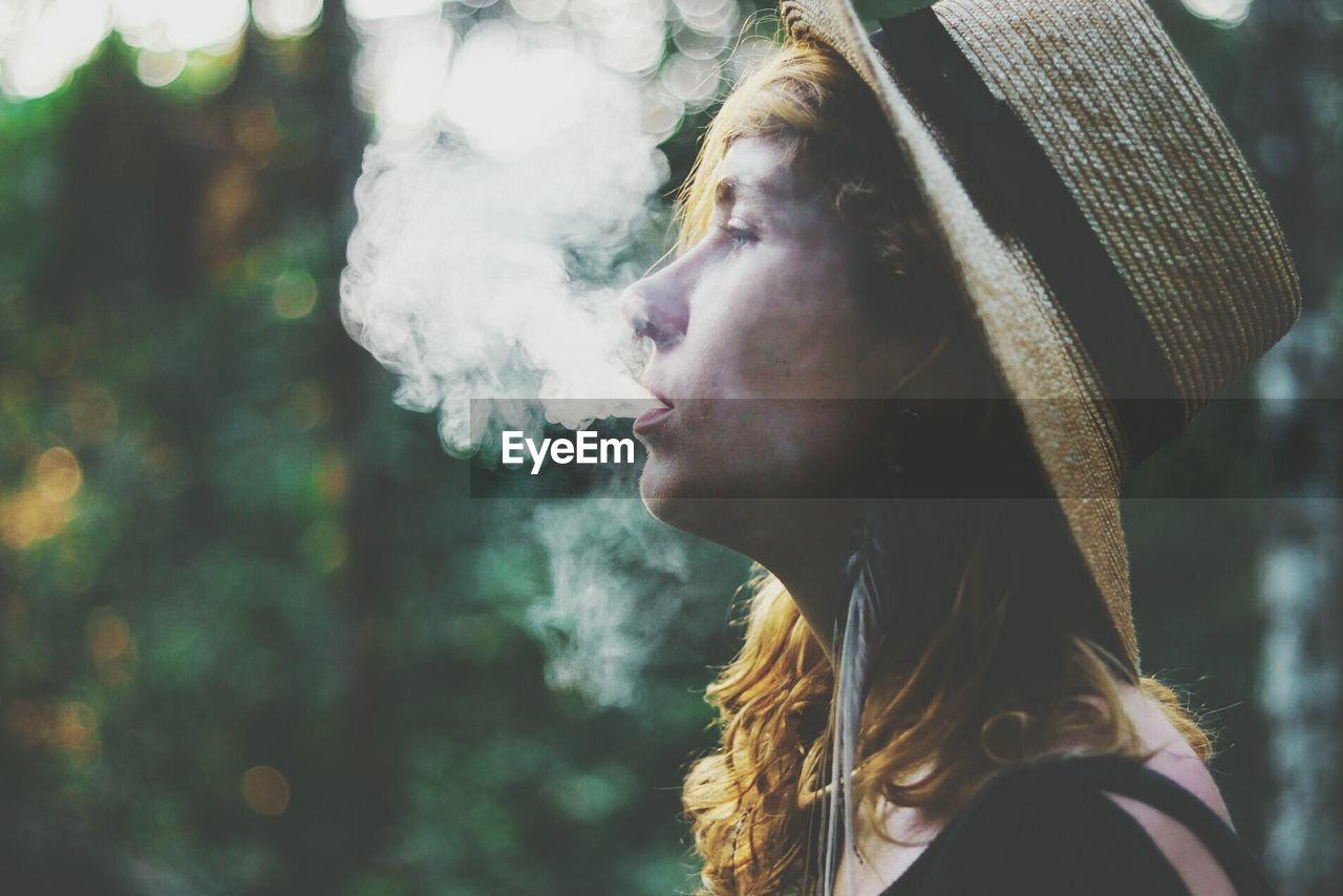 Close-up of woman exhaling smoke outdoors