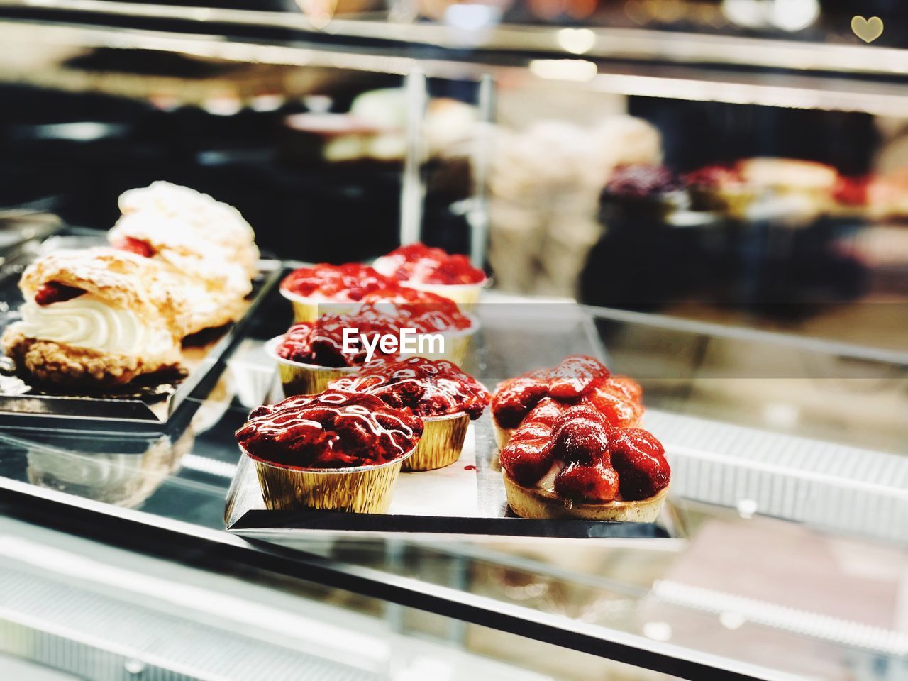 food, food and drink, freshness, sweet food, dessert, indulgence, sweet, indoors, store, still life, temptation, ready-to-eat, fruit, berry fruit, retail, unhealthy eating, no people, focus on foreground, plate, strawberry, display cabinet, retail display, baked pastry item, tray, tart - dessert