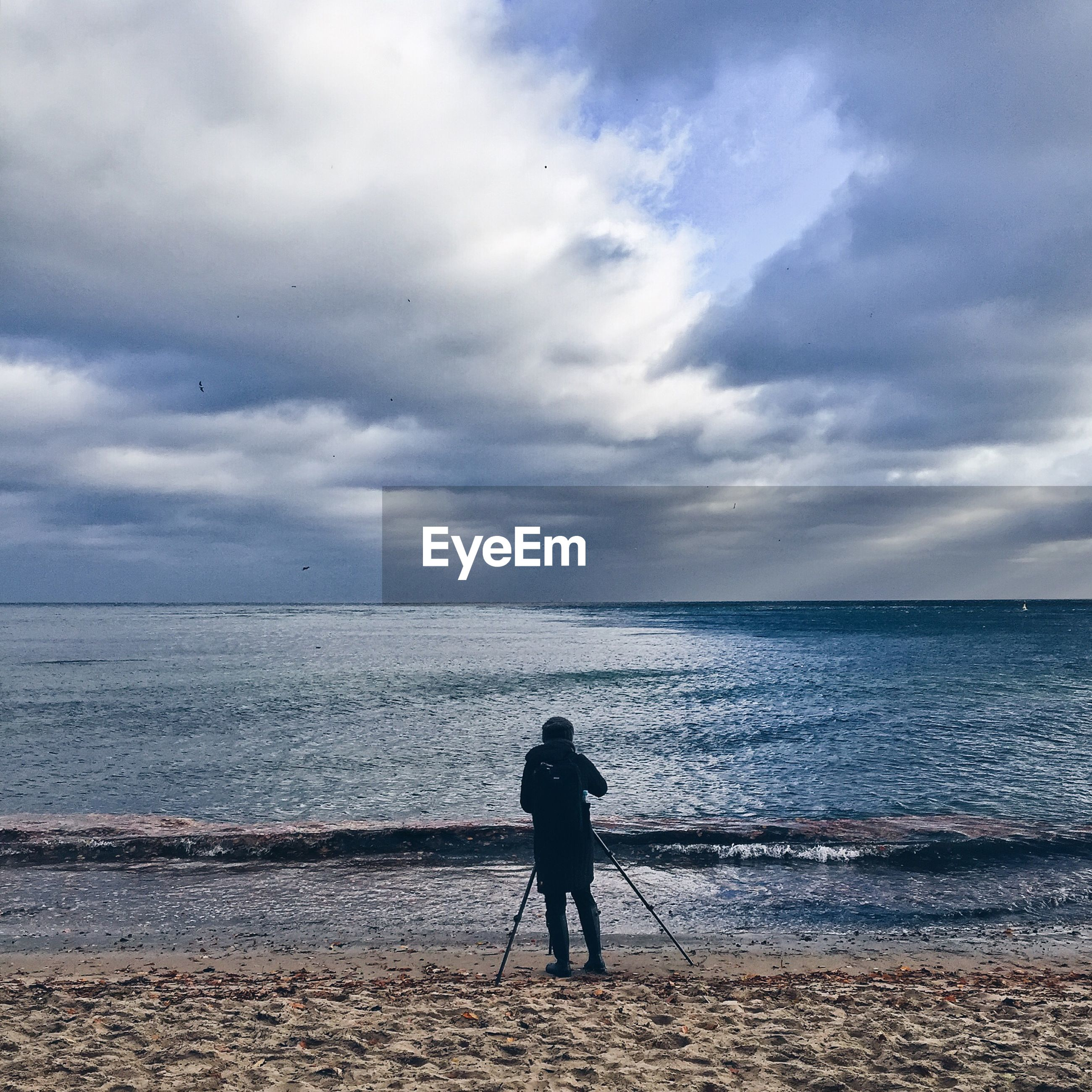 Rear view of person with hiking poles standing on shore against cloudy sky