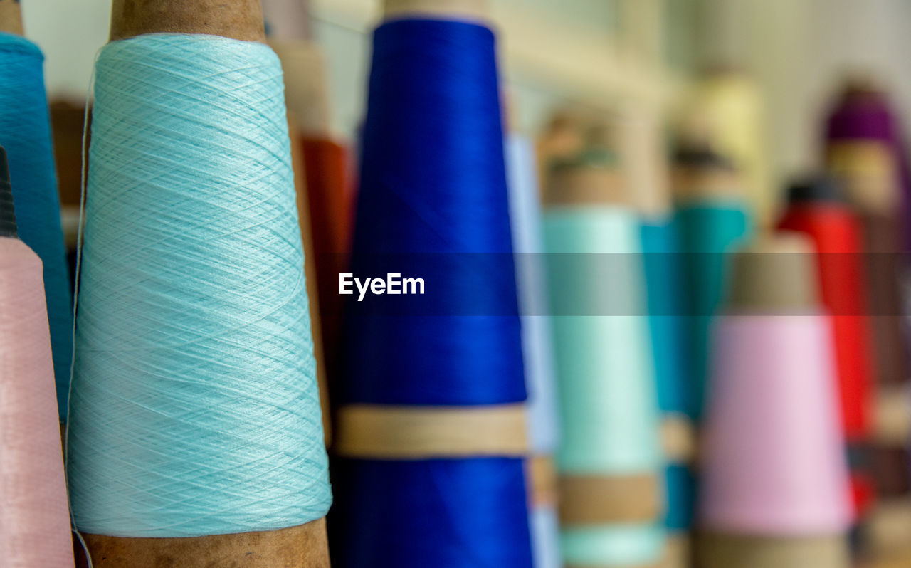 multi colored, choice, variation, close-up, art and craft, indoors, thread, focus on foreground, spool, textile, no people, creativity, still life, sewing item, rolled up, industry, selective focus, craft, textile industry, in a row, purple, art and craft equipment