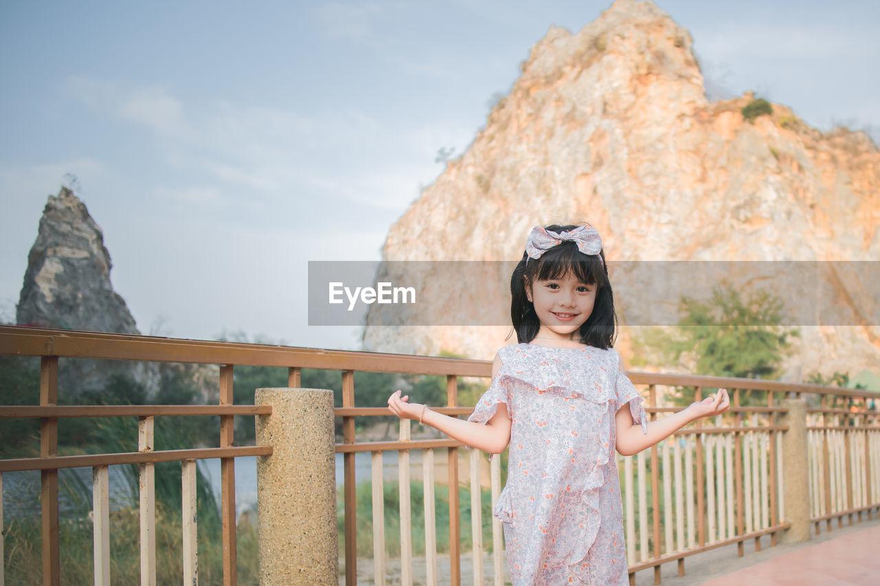 Portrait of cute girl standing against railing