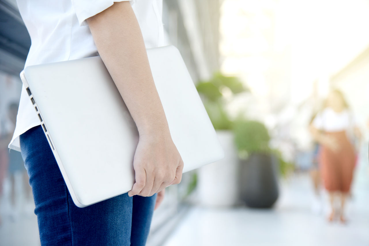 Midsection Of Woman Holding Laptop At Office