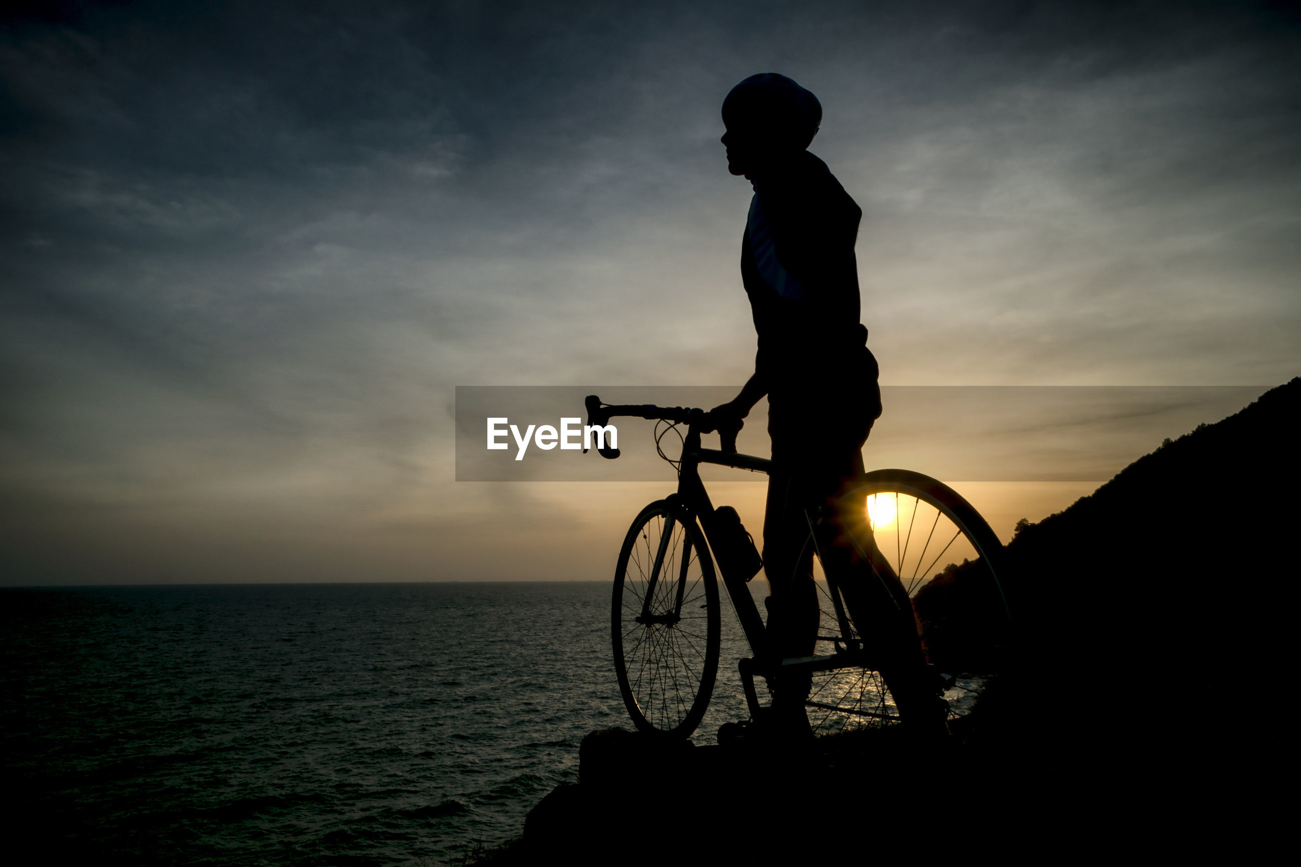 Silhouette man with bicycle at beach against sky during sunset