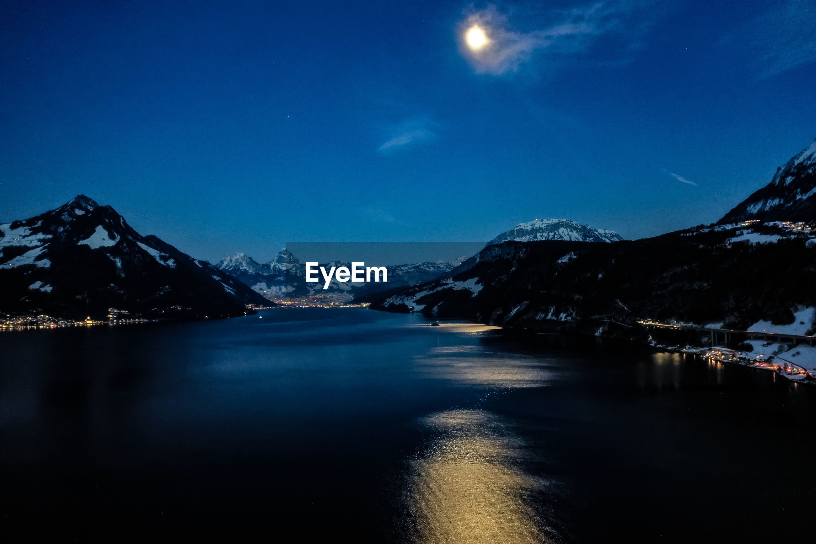 SCENIC VIEW OF LAKE BY ILLUMINATED MOUNTAIN AGAINST SKY AT NIGHT