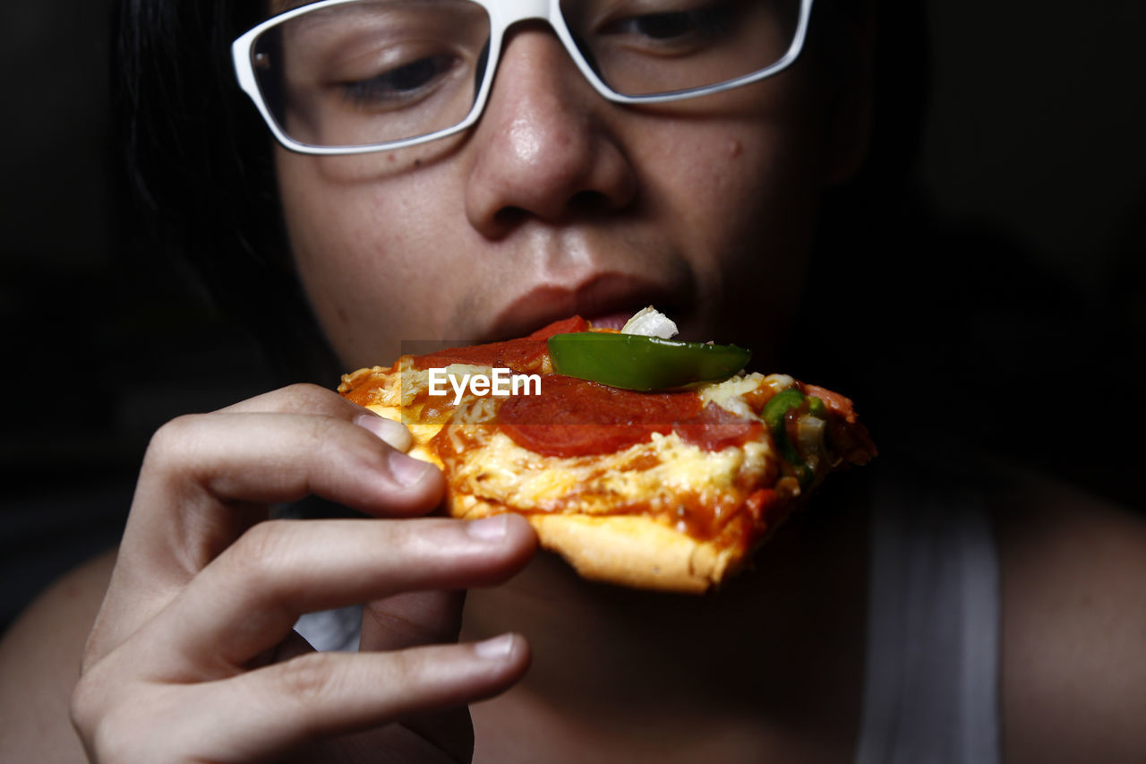 food, food and drink, eating, one person, real people, indoors, glasses, holding, young adult, eyeglasses, close-up, lifestyles, pizza, unhealthy eating, front view, headshot, freshness, portrait, leisure activity, ready-to-eat, teenager, adolescence, teenage boys, mouth open