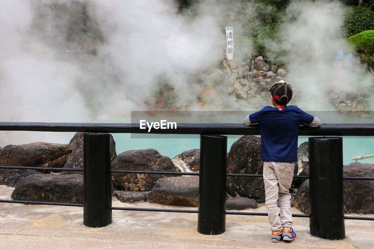 Rear view of boy looking at hot spring while standing by railing