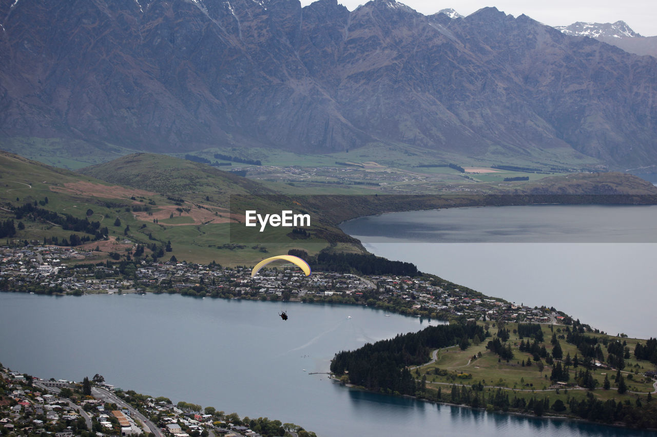 High Angle View Of Person Paragliding Against Lake