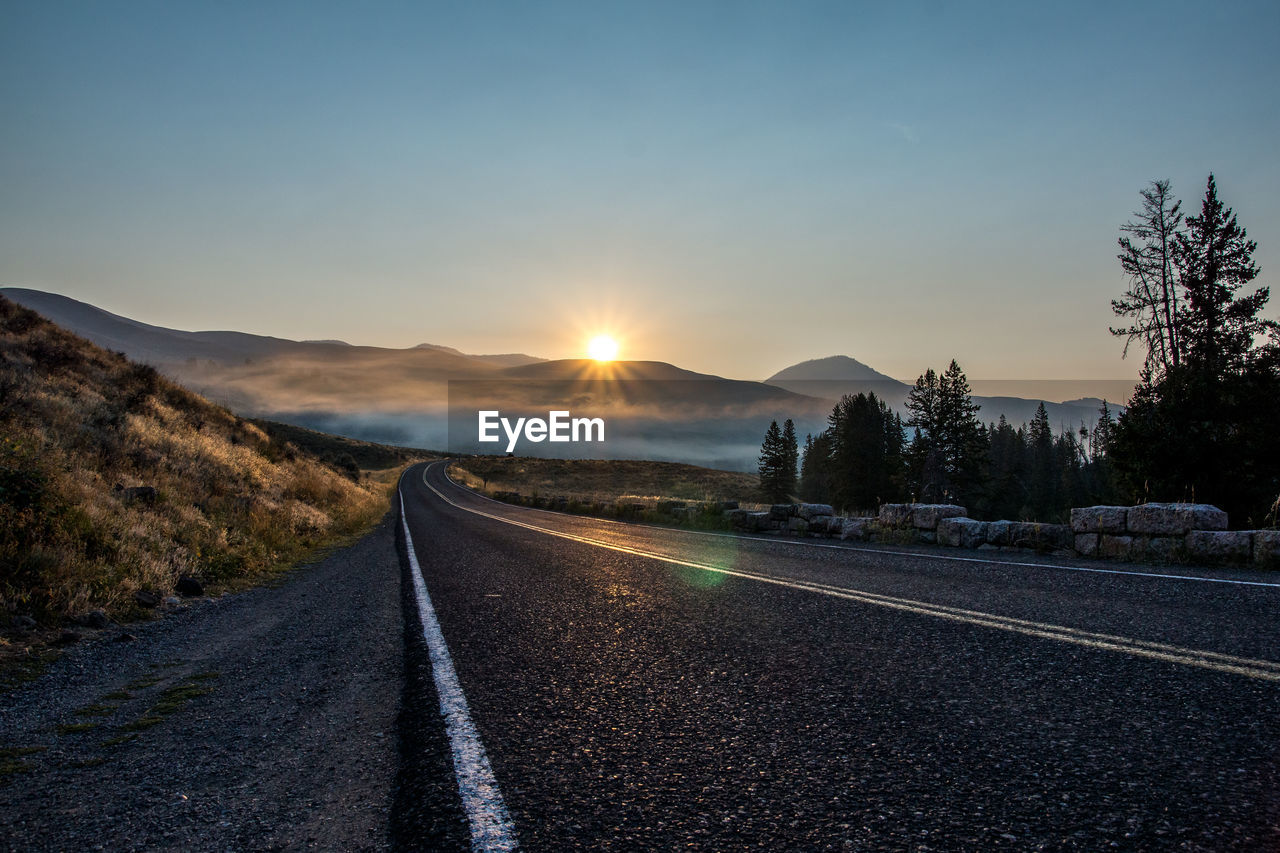 sky, road, direction, transportation, sunset, the way forward, nature, sunlight, symbol, sun, tree, road marking, marking, beauty in nature, sign, scenics - nature, no people, mountain, plant, tranquil scene, diminishing perspective, lens flare, outdoors, dividing line