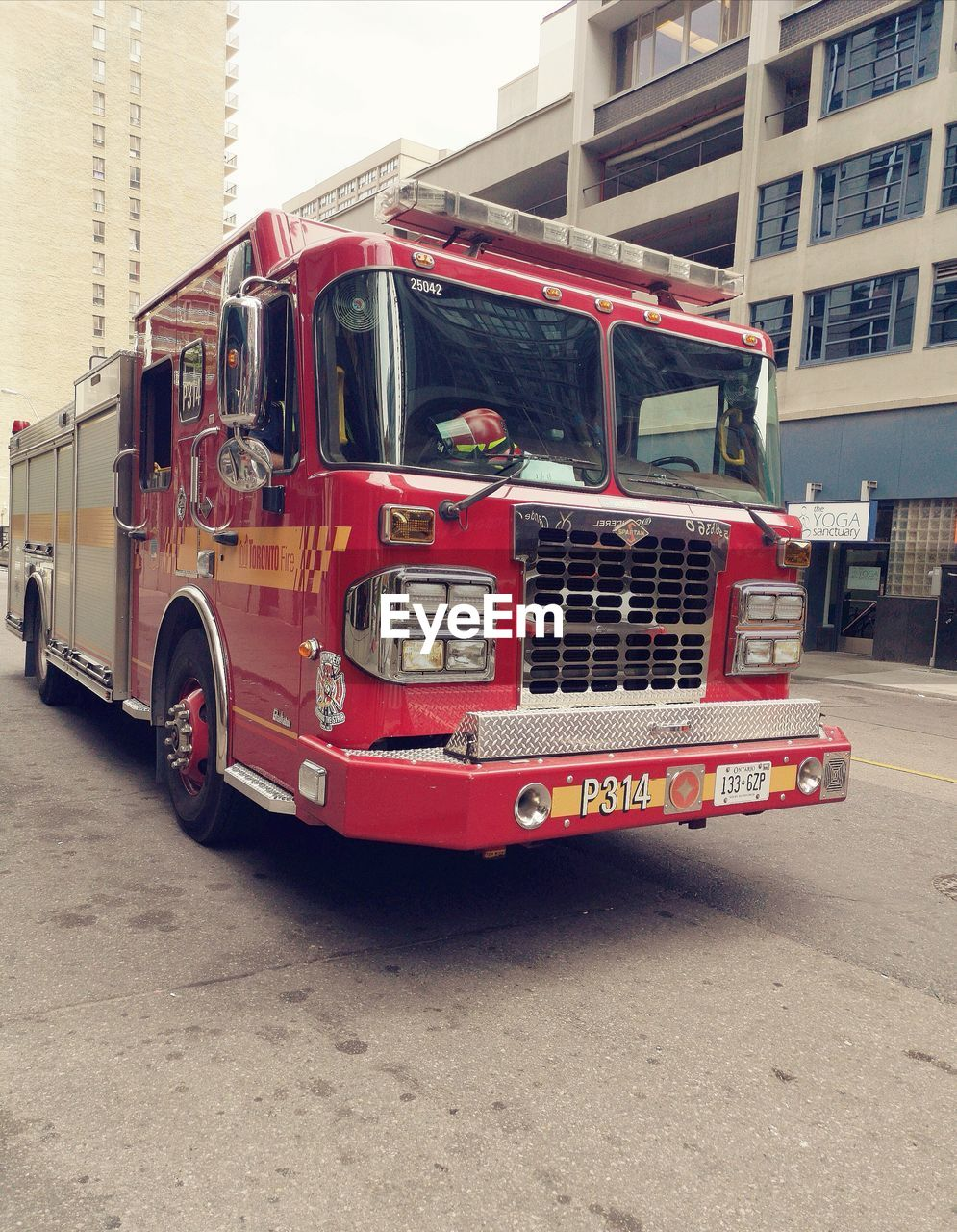 transportation, land vehicle, mode of transportation, red, architecture, building exterior, city, built structure, street, fire engine, day, road, public transportation, rescue, truck, building, no people, outdoors, motor vehicle