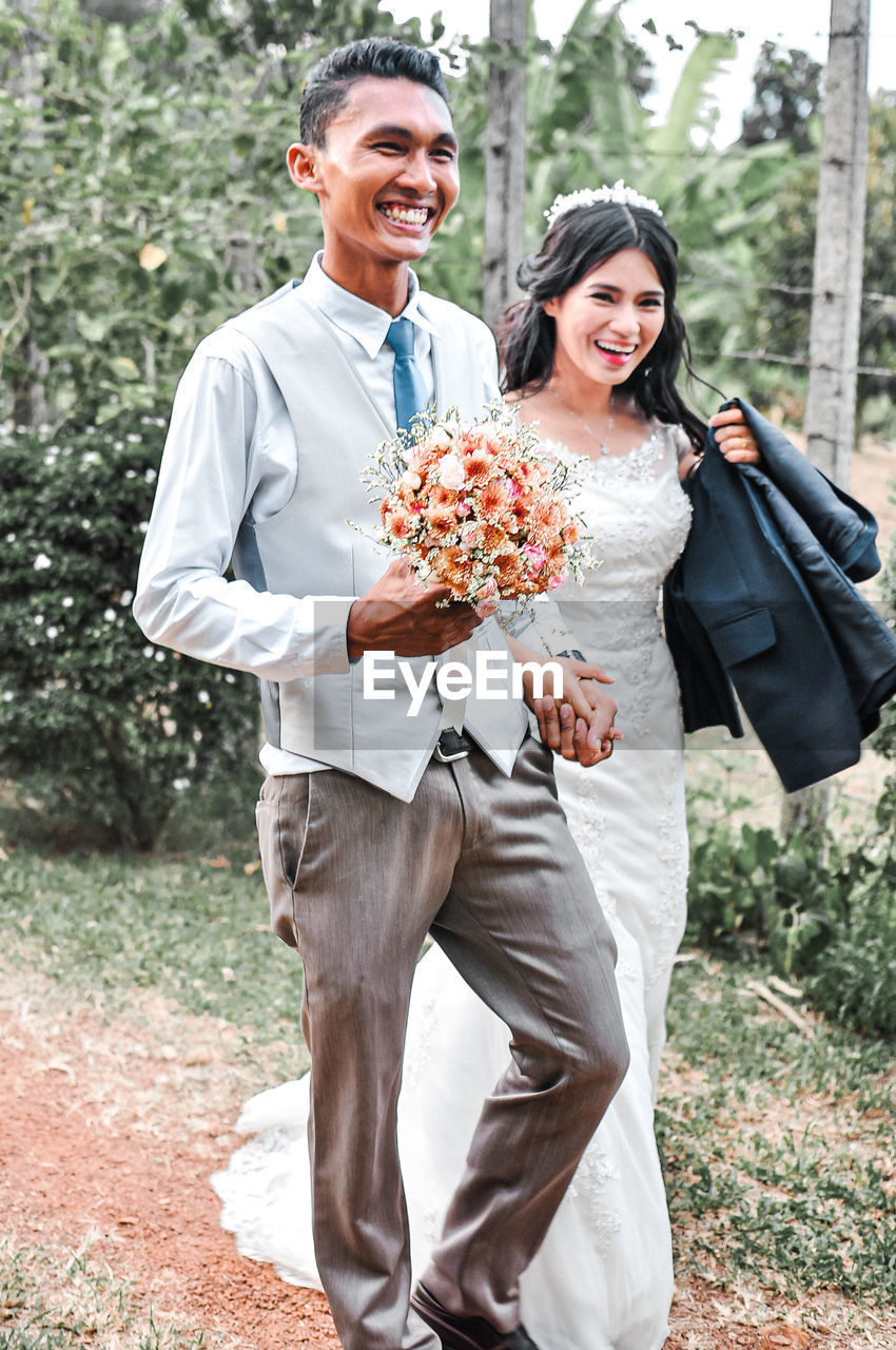 Portrait of married couple holding bouquet walking outdoors