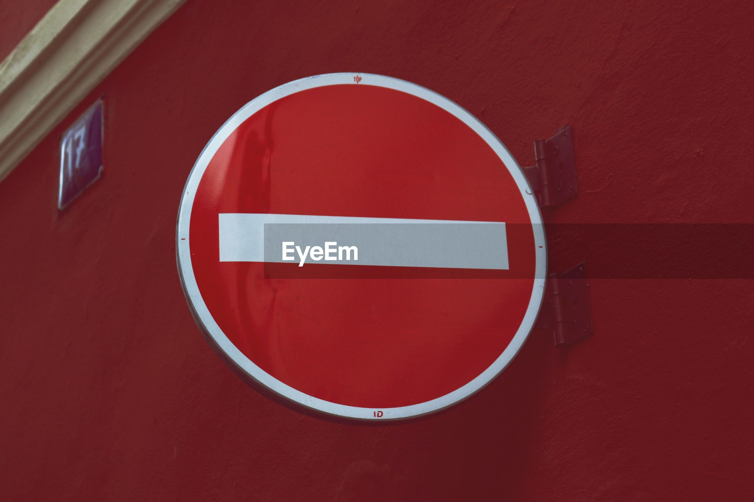 Close-up of sign on red wall