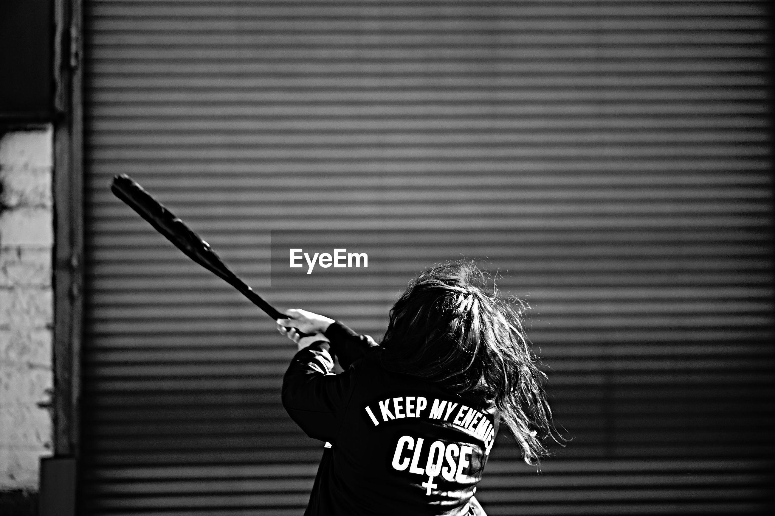 Rear view of girl playing with baseball against shutter