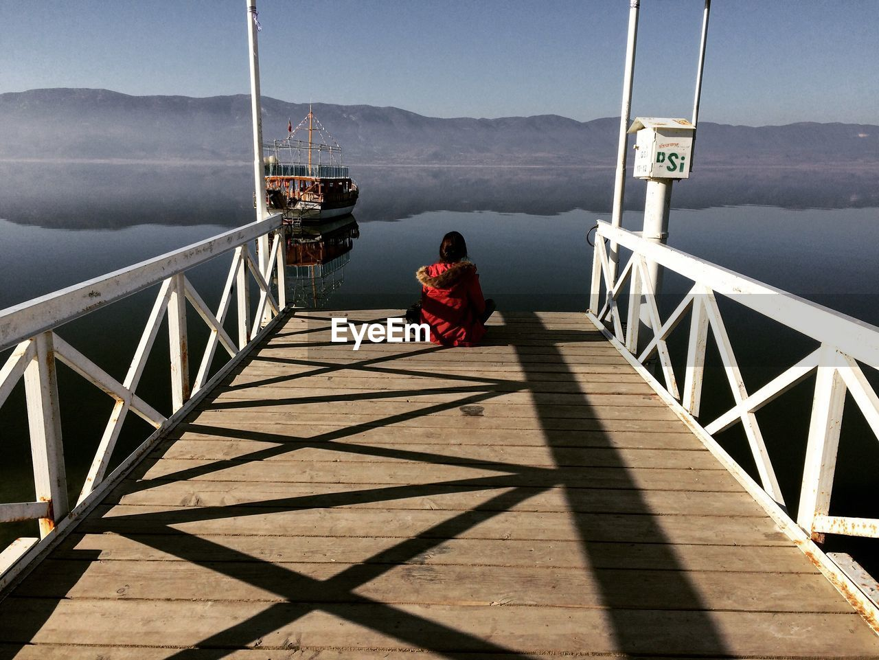 Rear View Of Woman Sitting On Pier Against Lake