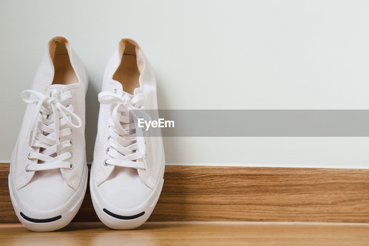 Close-up of canvas shoes on hardwood floor against white wall