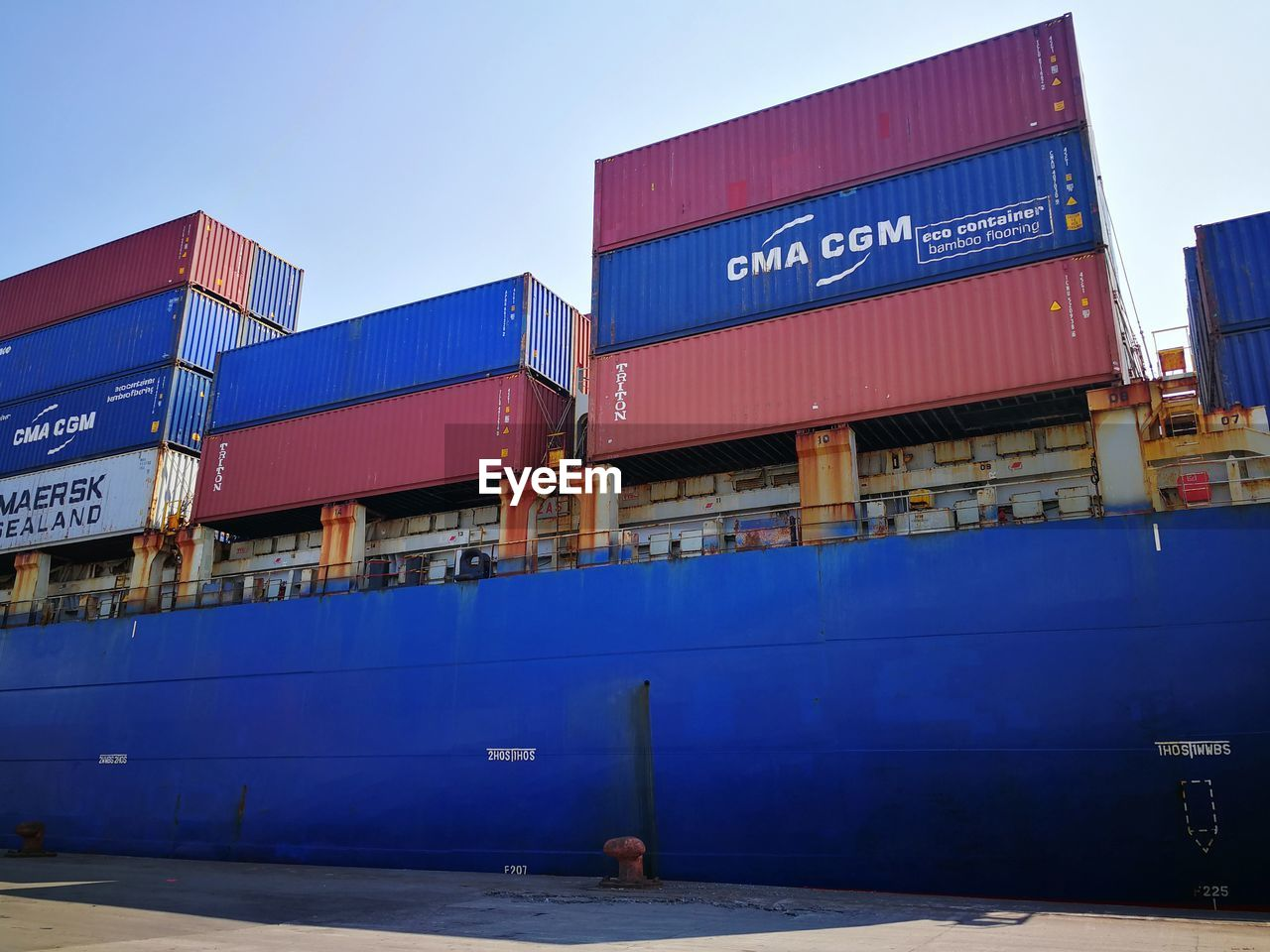 sky, blue, architecture, text, transportation, freight transportation, nature, cargo container, built structure, pier, no people, building exterior, business, day, industry, western script, outdoors, commercial dock, communication, clear sky