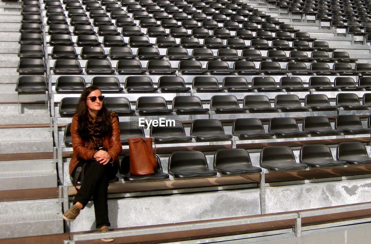 Woman Sitting On Bleachers At Stadium