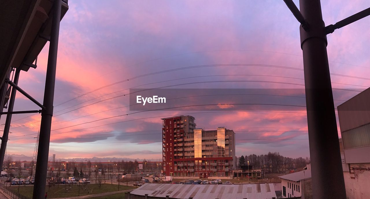 sky, architecture, built structure, building exterior, sunset, cloud - sky, nature, city, no people, building, fuel and power generation, outdoors, residential district, cityscape, orange color, environmental conservation, beauty in nature, low angle view, connection