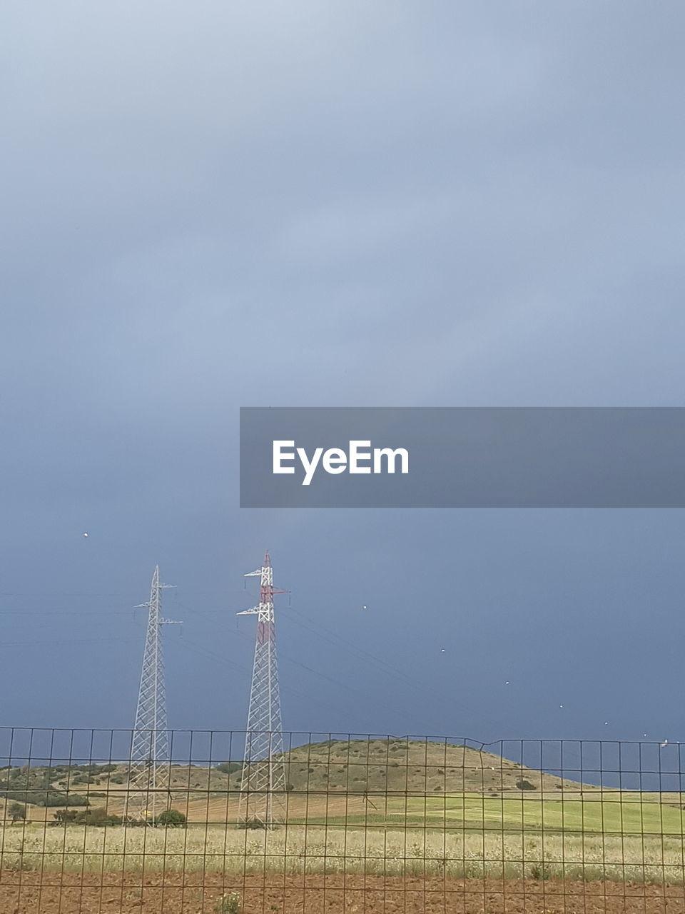 CRANE ON FIELD AGAINST SKY