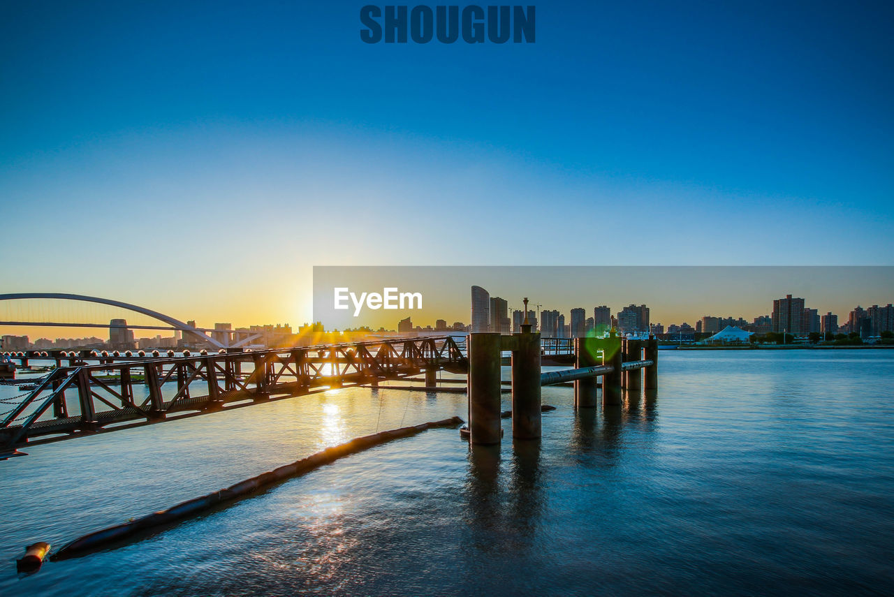 architecture, built structure, building exterior, bridge - man made structure, river, city, water, sky, outdoors, travel destinations, sunset, illuminated, sunlight, no people, cityscape, blue, skyscraper, clear sky, nature, day