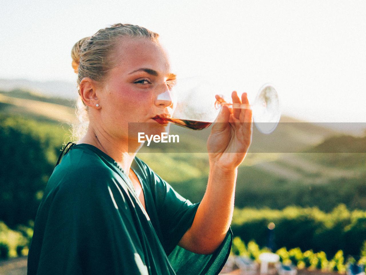 Portrait of woman drinking wine against landscape