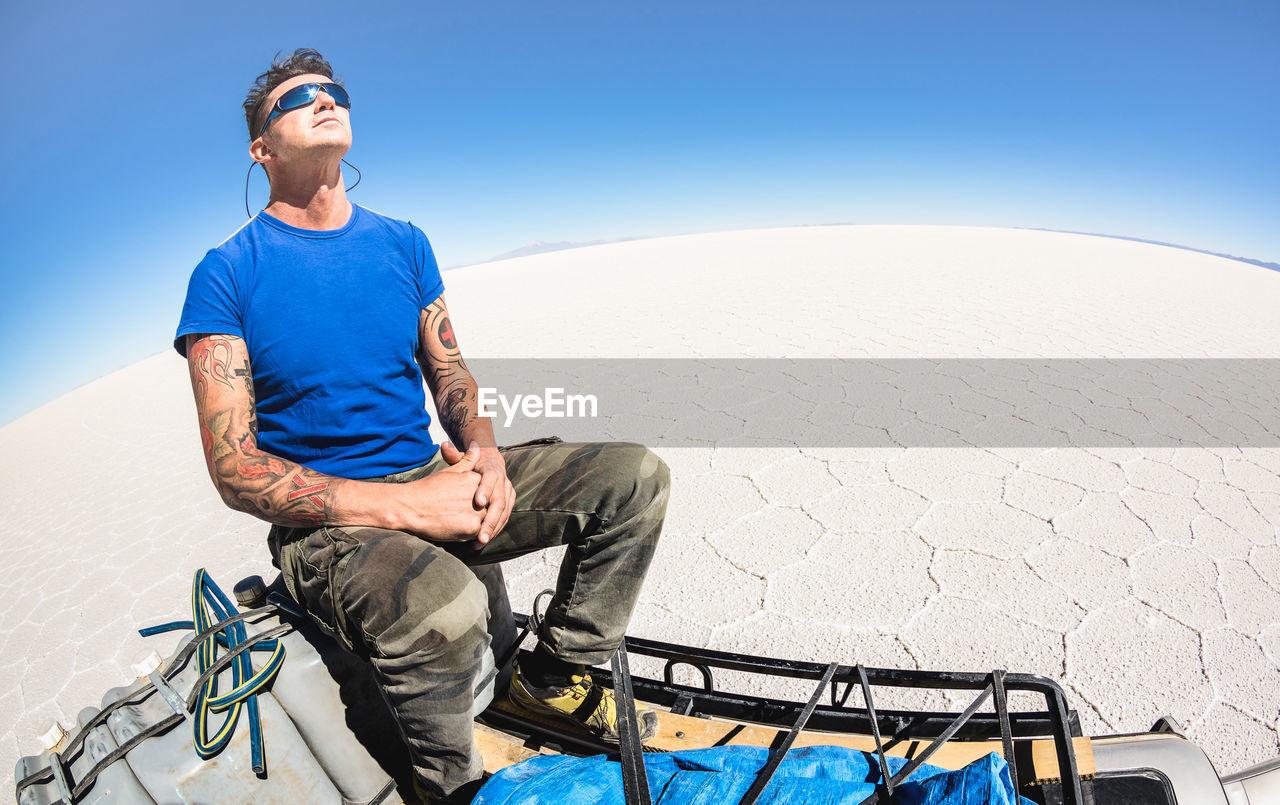 Man Sitting On Off-Road Vehicle Against Clear Blue Sky At Salar De Uyuni