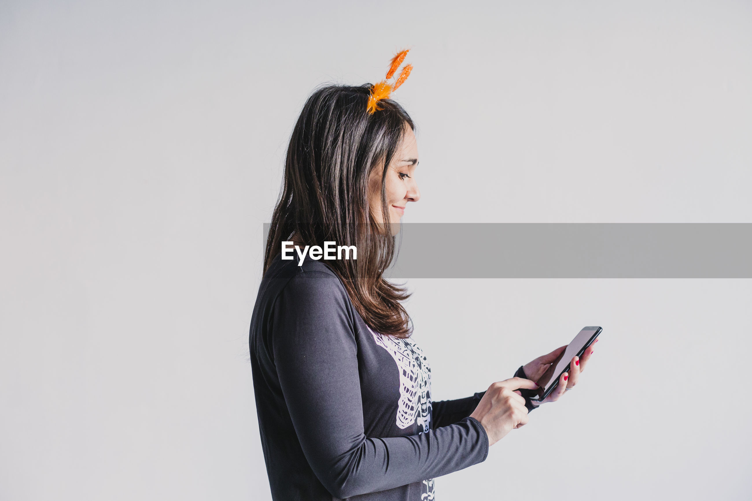 Side view of woman using mobile phone against white background