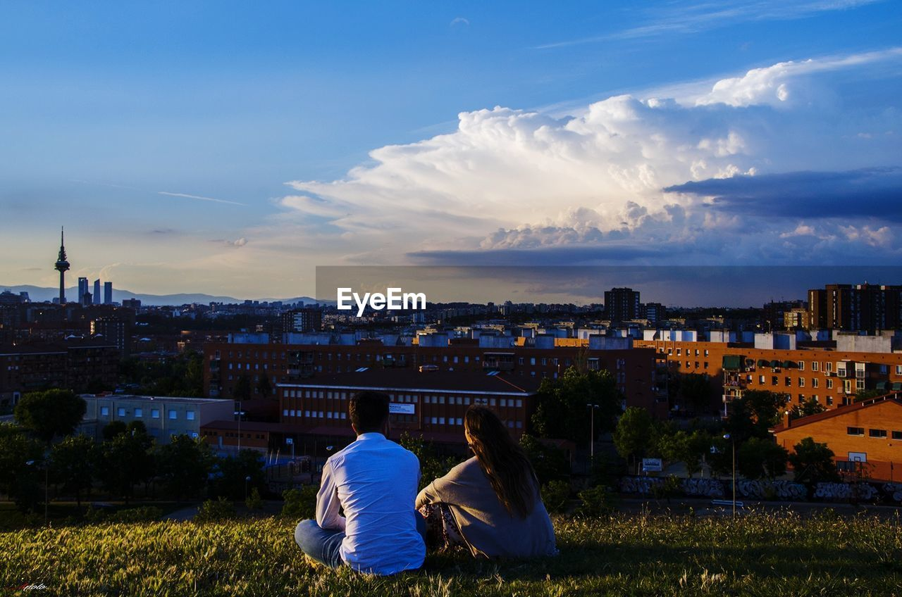 building exterior, architecture, built structure, sky, cloud - sky, city, rear view, real people, nature, men, grass, people, building, lifestyles, cityscape, leisure activity, plant, outdoors, day, residential district
