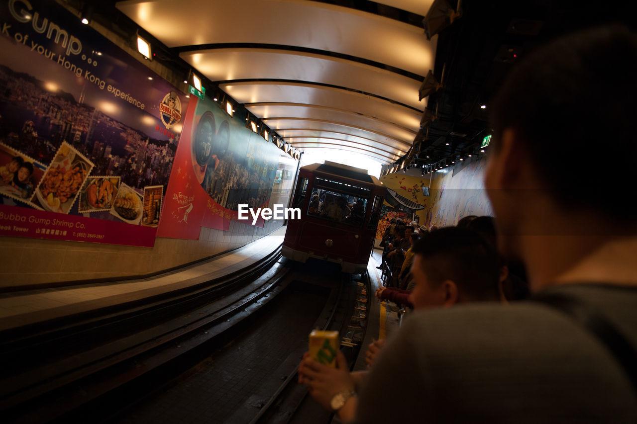 real people, rear view, transportation, men, leisure activity, lifestyles, public transportation, train - vehicle, illuminated, women, indoors, night