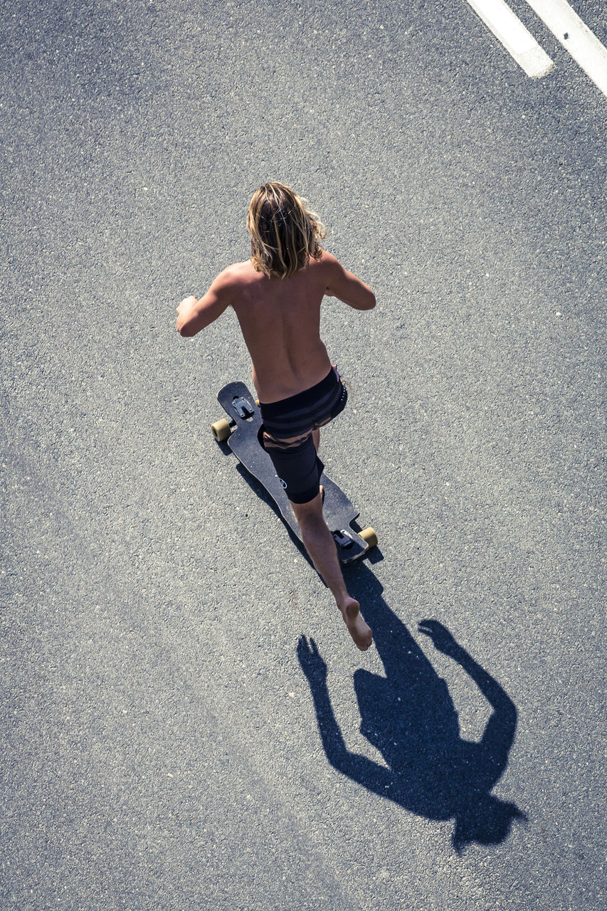 High angle view of shirtless man skateboarding on road