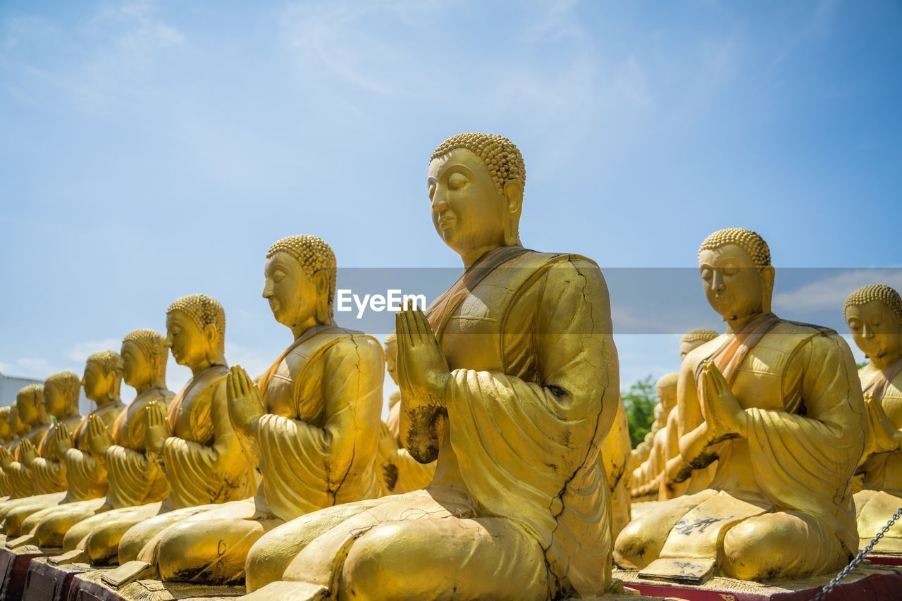 statue, religion, male likeness, sculpture, human representation, sky, spirituality, art and craft, representation, belief, no people, creativity, idol, day, low angle view, nature, architecture, gold colored