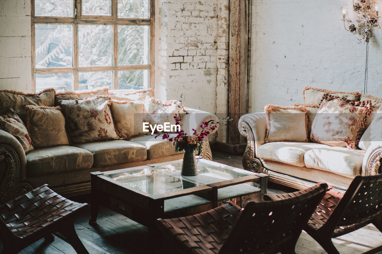 sofa, furniture, indoors, pillow, no people, chair, seat, day, absence, home interior, table, window, domestic room, cushion, living room, architecture, relaxation, built structure, stuffed, nature, coffee table